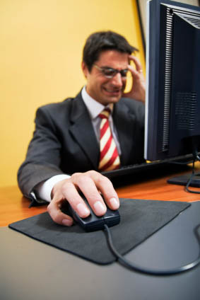 Frustrated man sitting at computer trying to rember his passwords